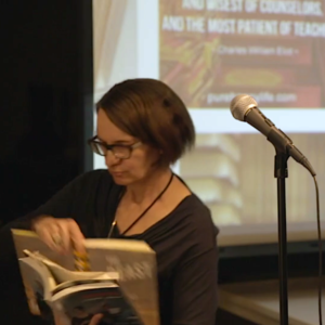 The photo shows a woman with a stack of open books in her arms. There is a microphone to the right.