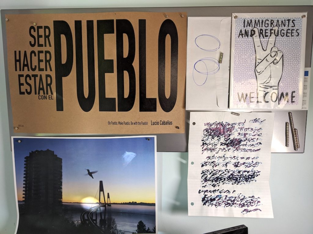 """A magnetic board with various papers afixed with magnets. One says """"Pueblo"""" another says """"Immigrants and Refugees Welcome"""". The mail art by Granados is next to a photo of a hummingbird at the level of a highrise above a bridge in New Westminster."""