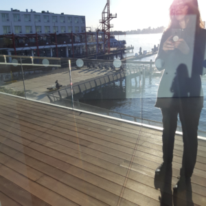 A woman is shown on right taking a photo of her own reflection in a window. Another reflection of herslef appears in her shadowy image. In the background there is a wooden peir and a dock. Burrard Inlet is seen in the background.