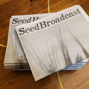 Staks of SeedBroadcast newsprint journals on wood tabletop